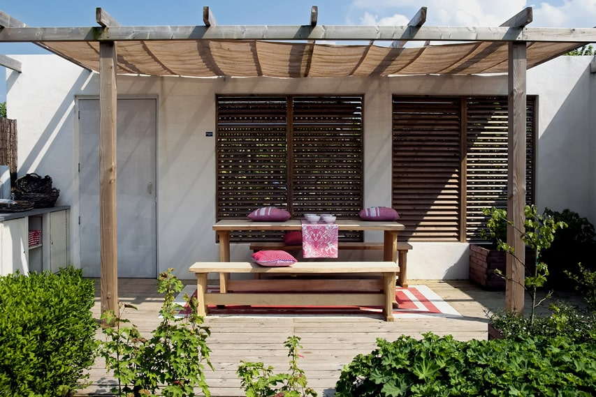 Garden patio area with rustic charm and wood pergola and picnic table