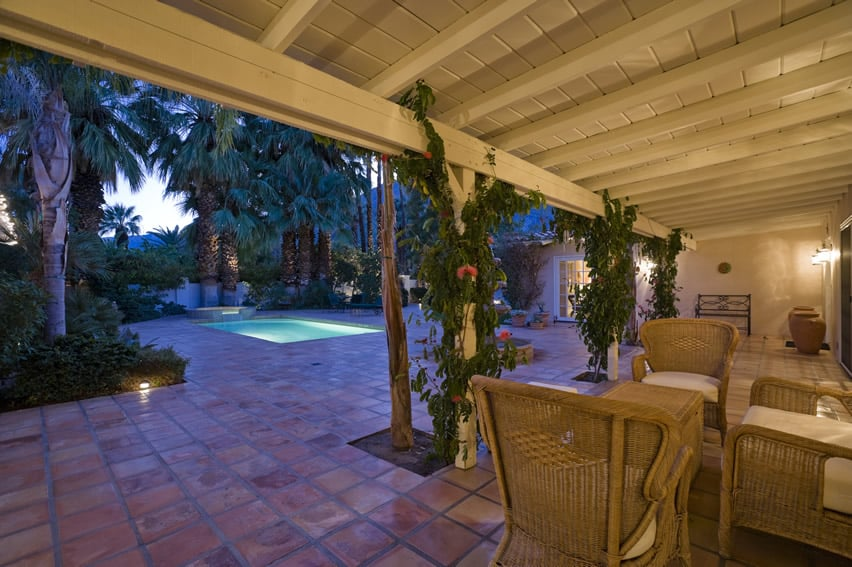 Classic covered garden patio design with Spanish style terra cotta red paving tiles and creeping vines