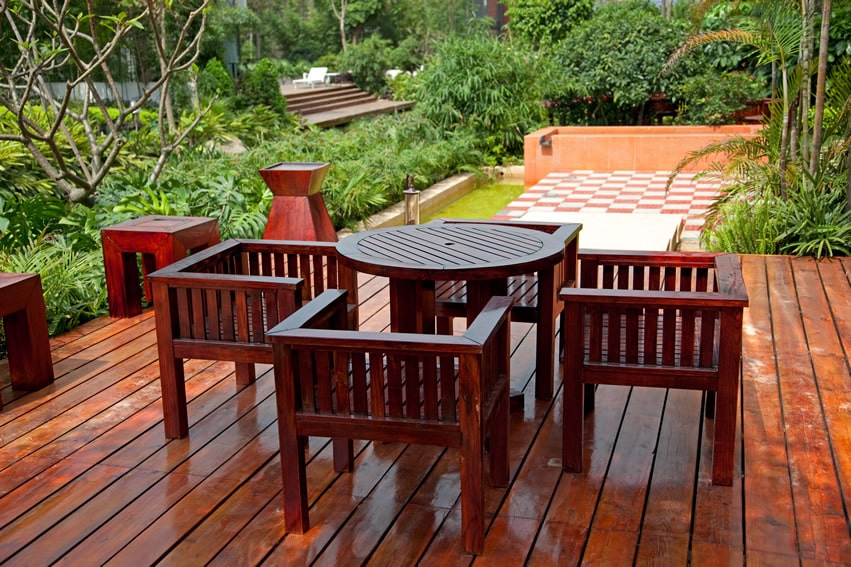 Stained wood deck with lush garden backyard