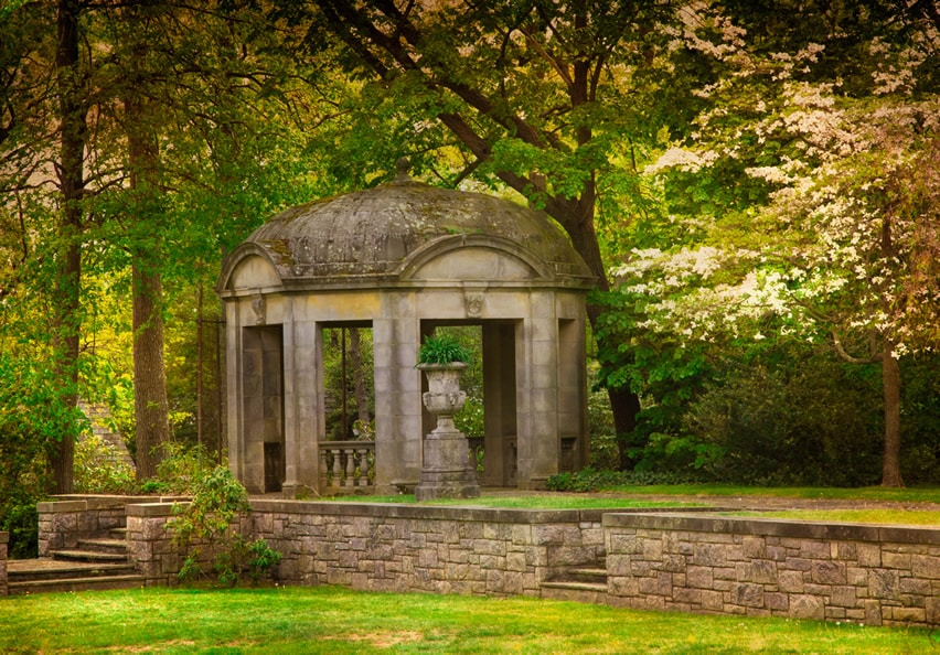 Stone gazebo under trees in park