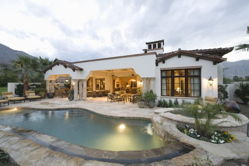 Stone swimming pool and hot tub view at spanish style house