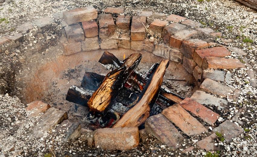 Sunken brick fire pit in backyard