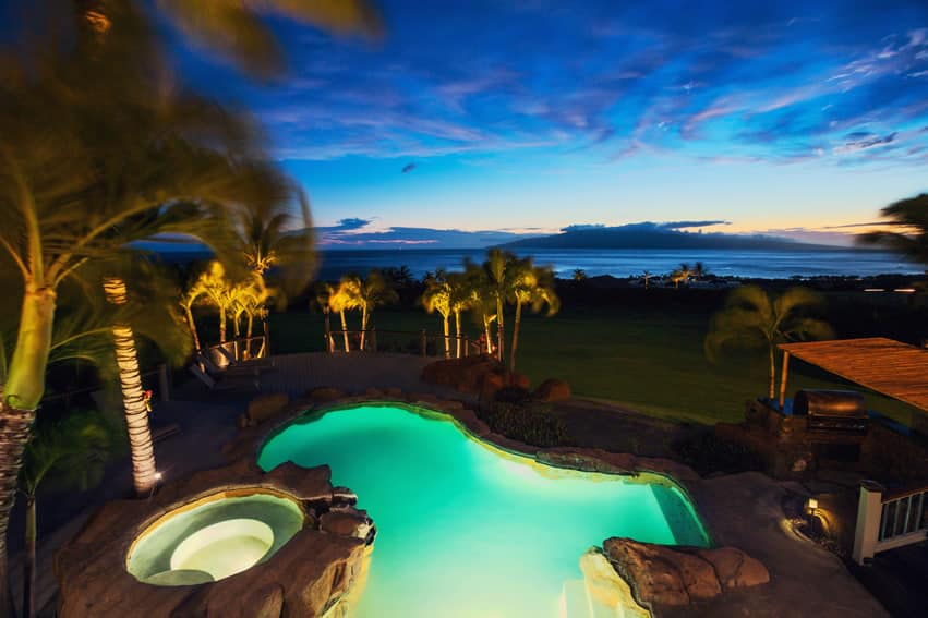 Swimming pool and spa with ocean view at night