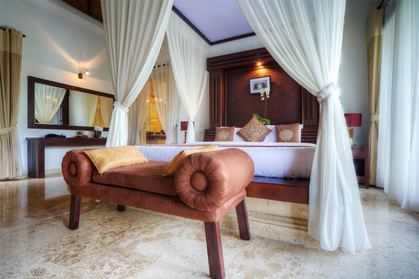 Tropical luxury bedroom with white canopy bed curtains