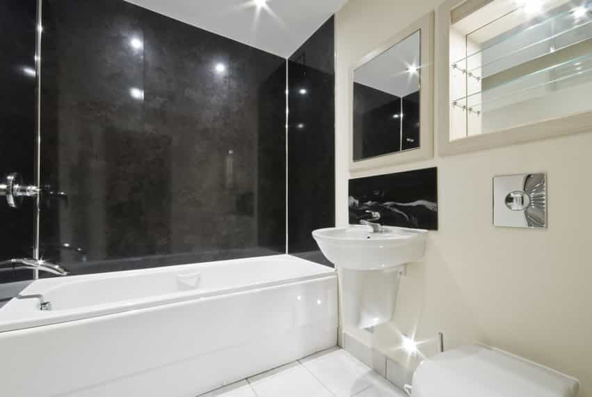 Sleek and simple, modern bath design, uses large black granite tiles on the bathtub/shower area walls