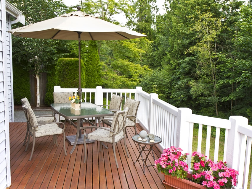 Wood deck with white railing posts and umbrella