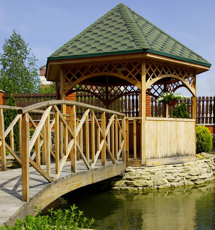 Wood gazebo across pond bridge