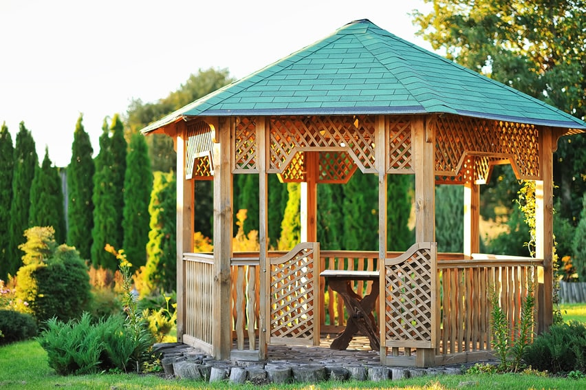 Wooden lattice gazebo with green top in garden area