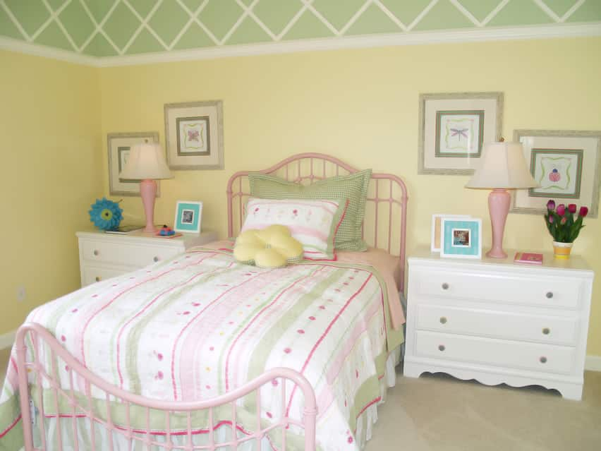 Colorful girl's bedroom with green and yellow walls and white furniture