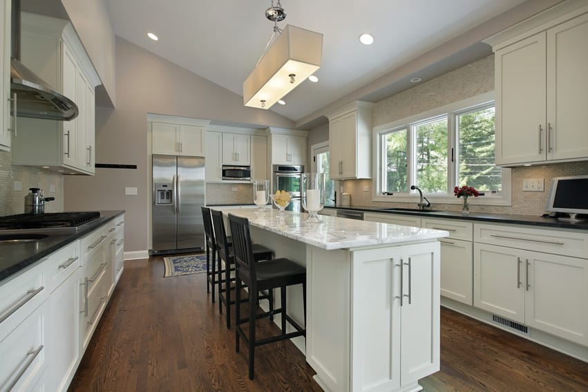 Attractive kitchen with white cabinets and marble island