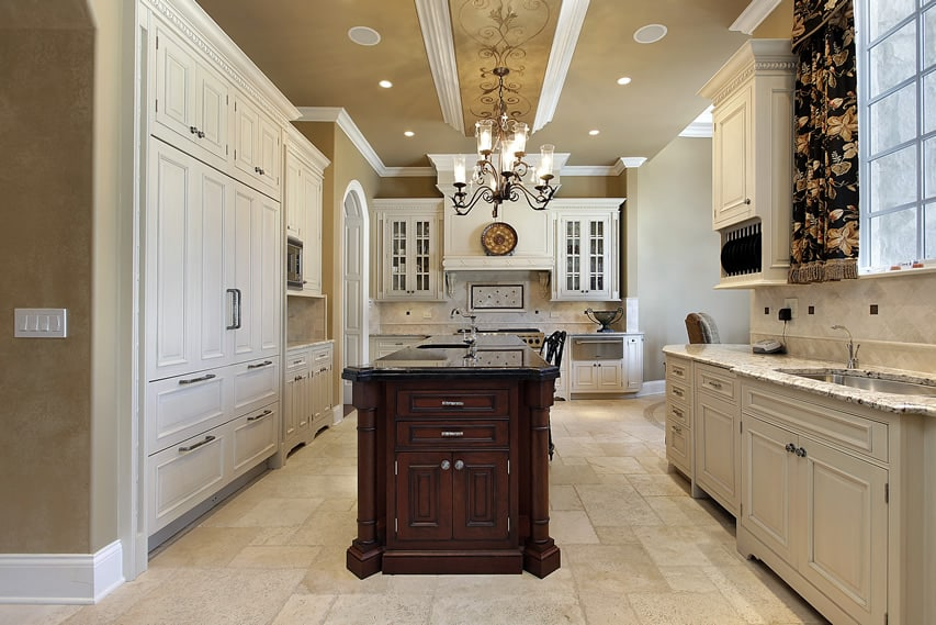 Elegant traditional kitchen in luxury home with white cabinets, dark cabinet island and double sinks