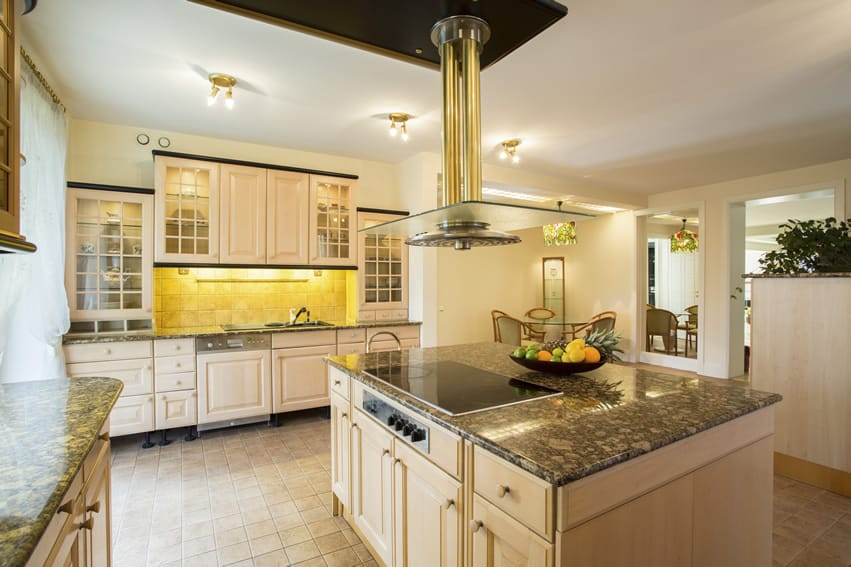 Granite counter kitchen with center island brass glass range hood