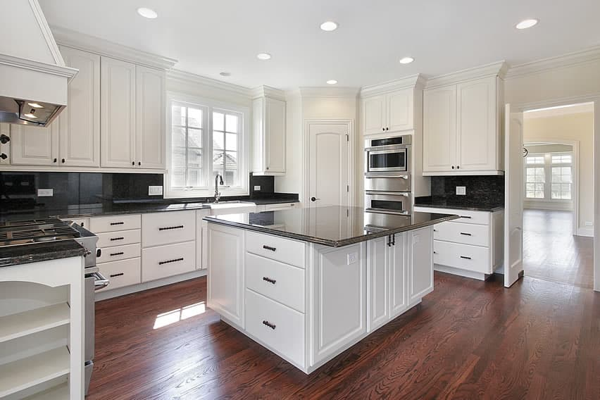 Kitchen with white cabinets dark granite counters
