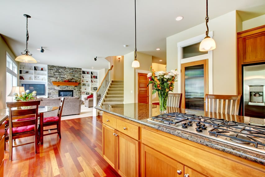 Luxury kitchen with cherry wood cabinets, flooring and island with range cooktop and granite counter