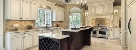 White luxury kitchen with granite island two chandeliers