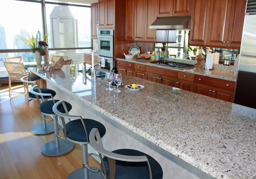 Long rectangular kitchen island with granite and barstools