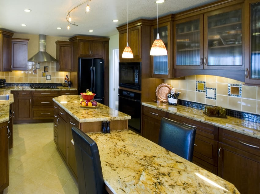 Long yellow granite two level kitchen island