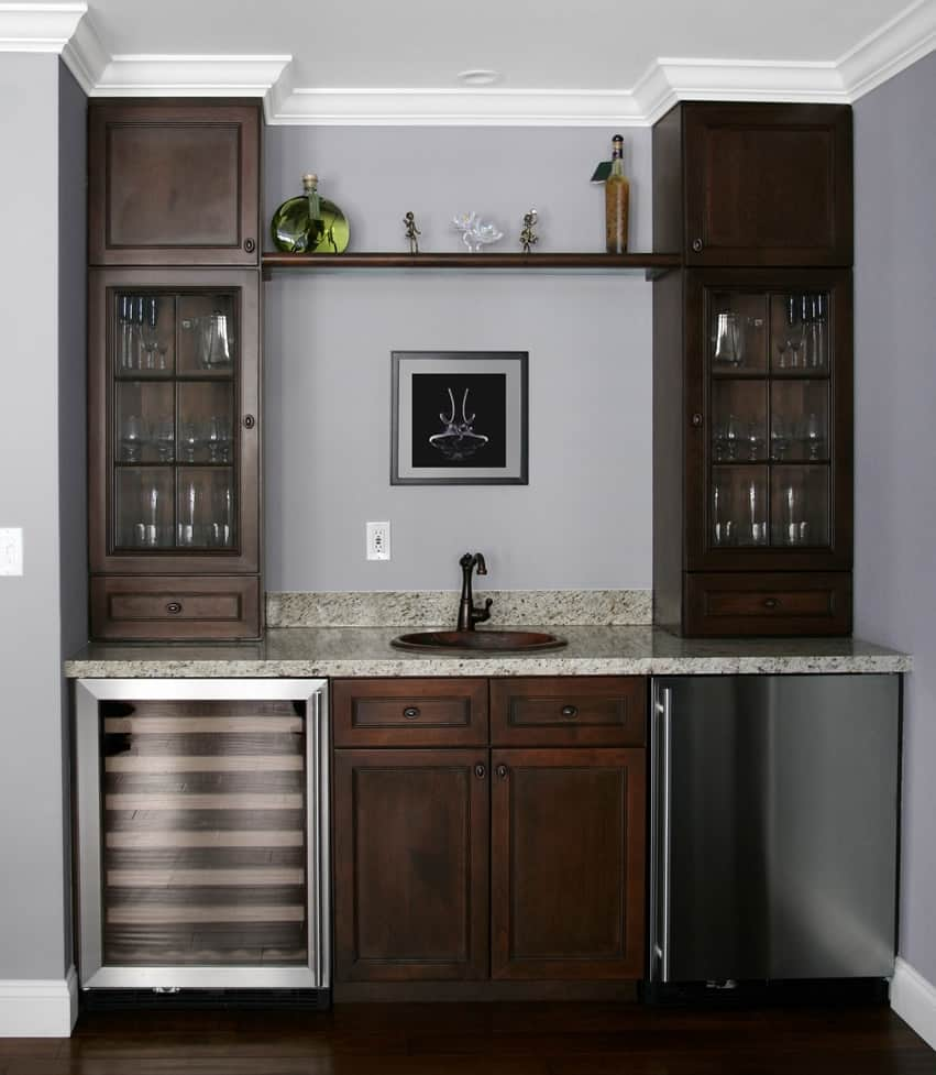 Wet bar in home with fridge, sink and cabinets