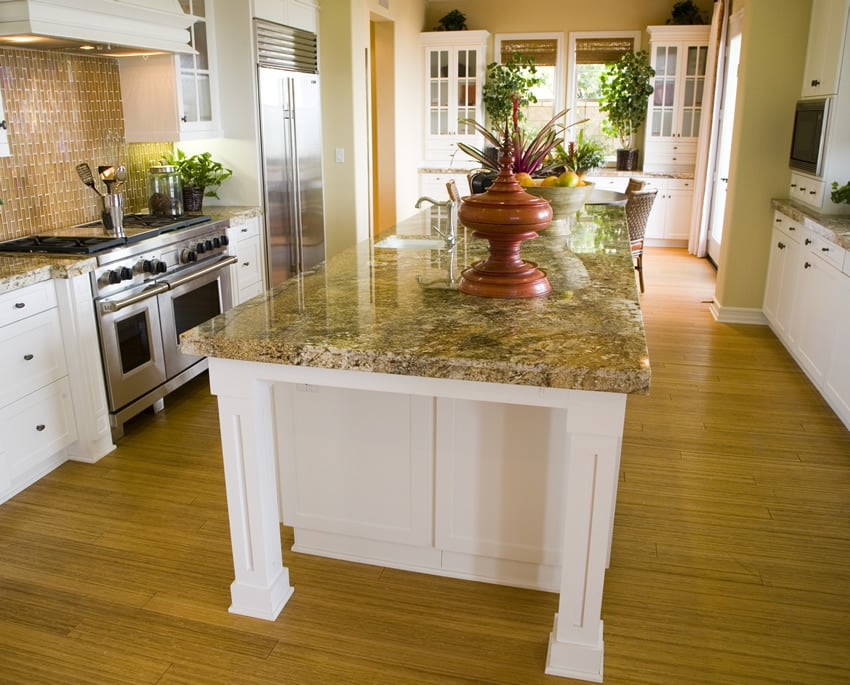 White kitchen island with full slab yellow granite counter top