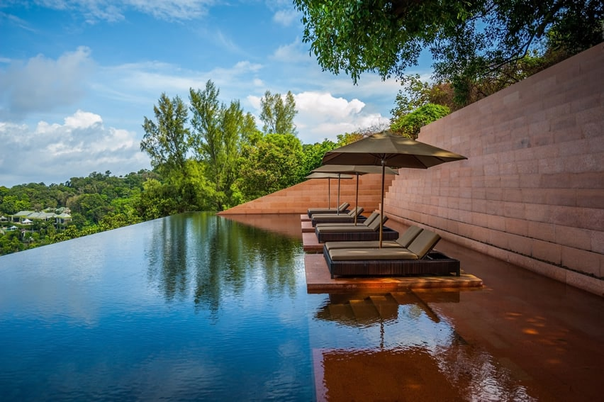 Amazing resort pool with lounge chairs above water