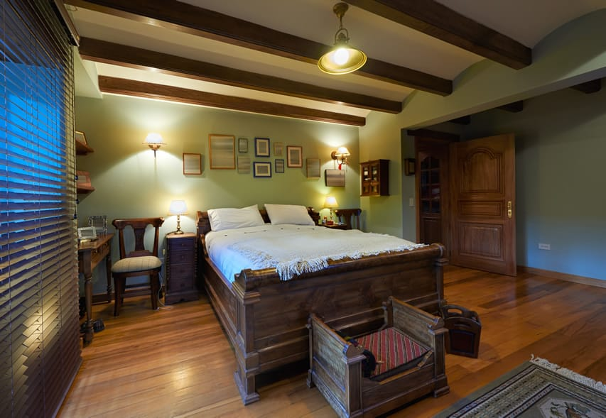 Bedroom with exposed beams and large wood frame bed