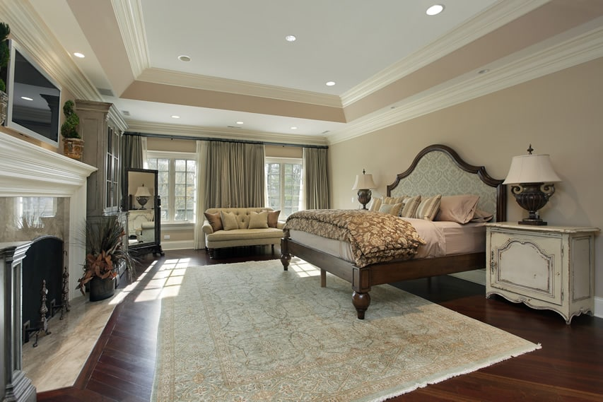 Bedroom with tray ceiling with fireplace and hardwood flooring