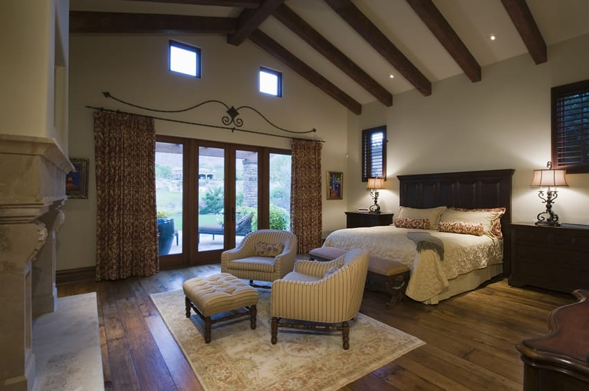 Bedroom with vaulted ceiling, exposed beams and large wood headboard