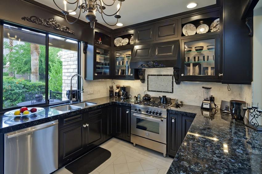 Black granite counter u-shape kitchen with dark cabinets