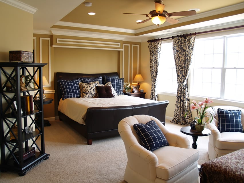 Carpeted bedroom with sleigh bed and sitting area