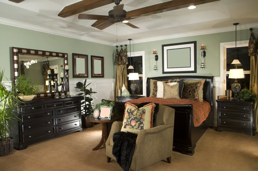 Designer decorated bedroom with wood sleigh bed and matching furniture