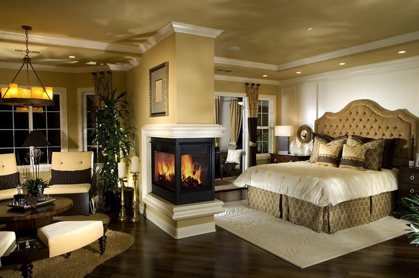 Designer master bedroom with fireplace in center