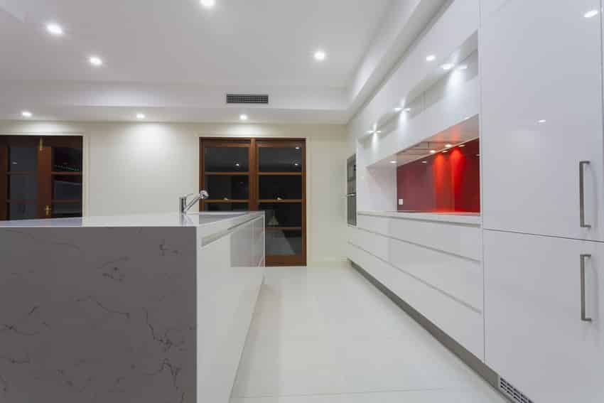 Double line kitchen in white with red accent back splash