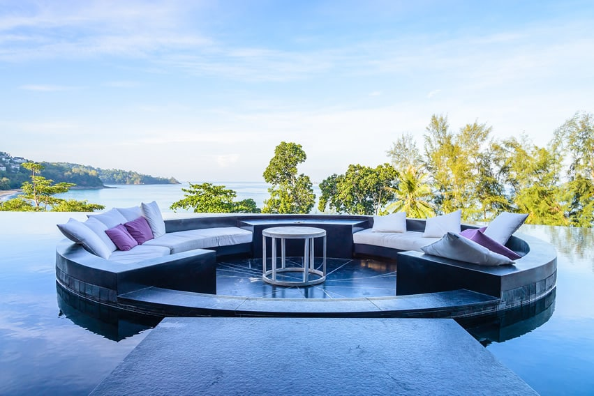 Large infinity pool with outdoor furniture and ocean view