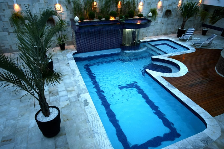 Luxury swimming pool with water feature and wood deck