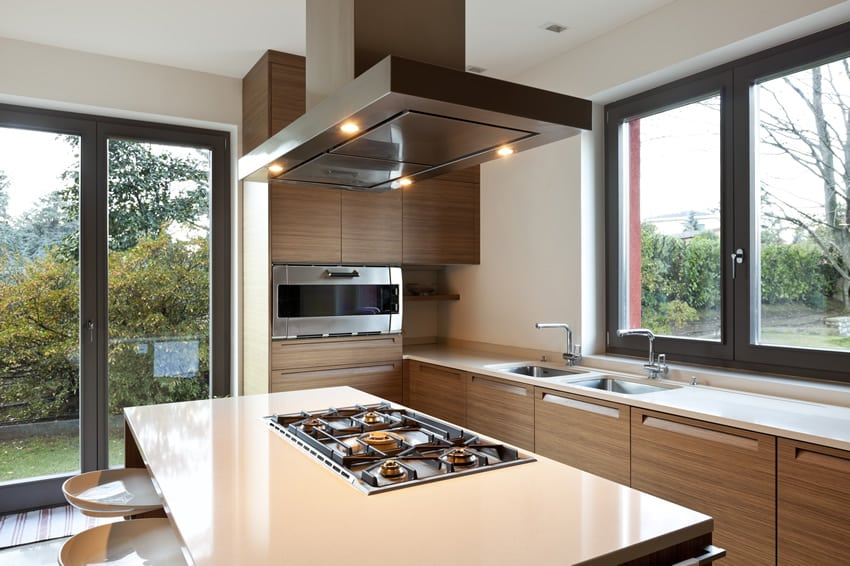 Modern home kitchen with brown cabinets and stove in island