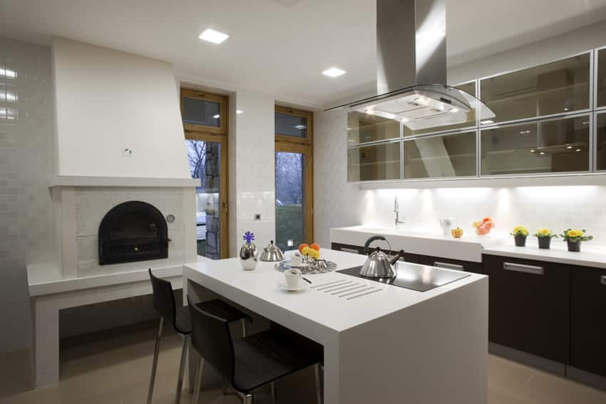 Modern kitchen with black cabinets, white counter and fireplace