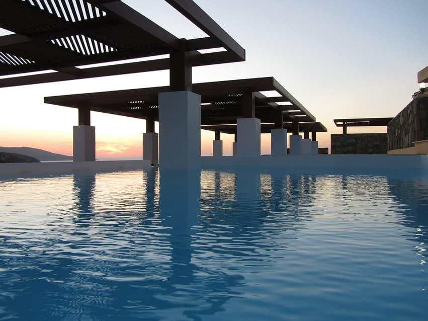 Modern swimming pool with white pillars overlooking ocean