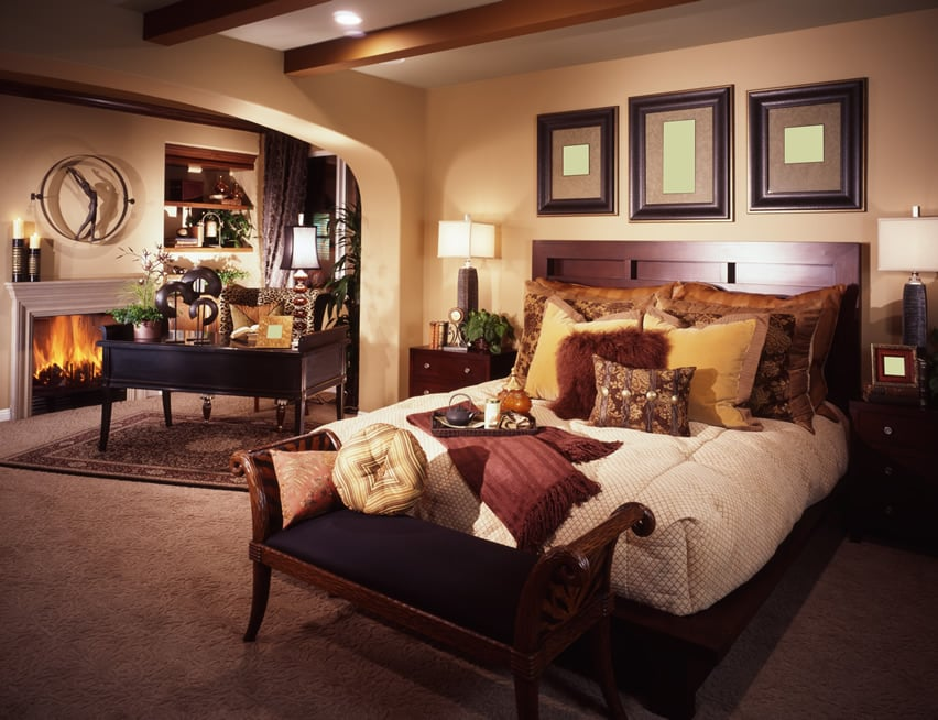 Refined bedroom with fireplace and exposed wood beams
