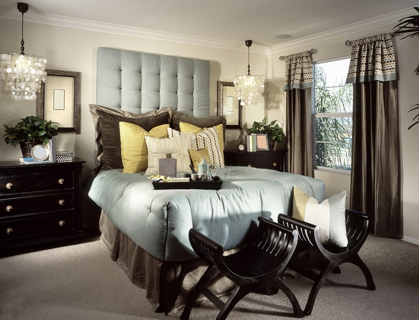 Richly decorated bedroom with blue upholstered headboard
