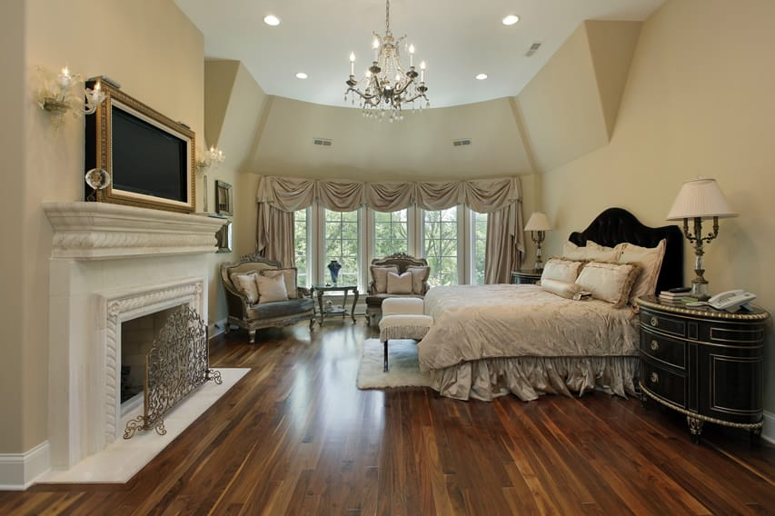 Richly decorated master bedroom with white fireplace
