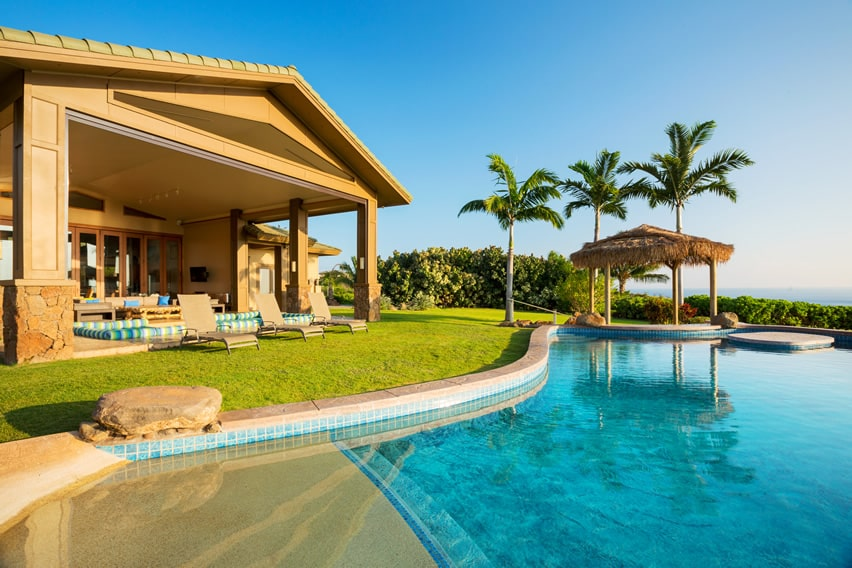 Swimming pool with faux sand and palapa