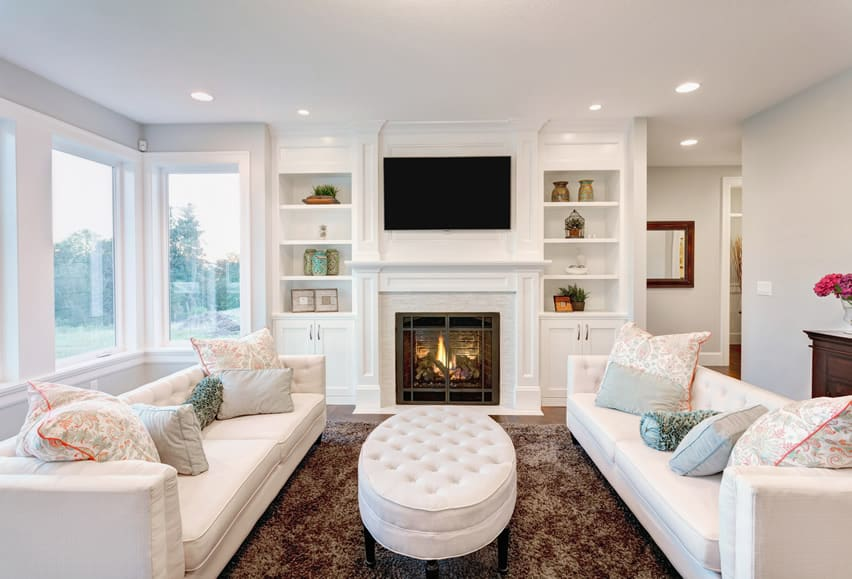 white theme living room with built in shelving and fireplace built living room