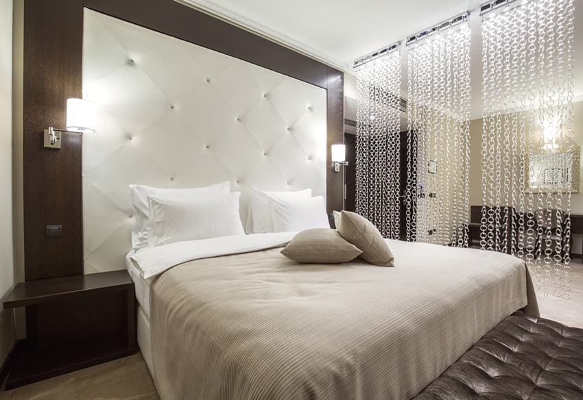 Attractive bedroom with large leather headboard chain curtain