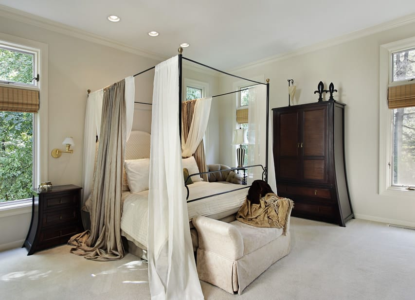 Beautiful four post bedroom with white curtains and interesting furniture pieces