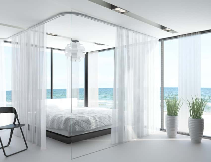 Bedroom on the ocean with white theme and bed curtains