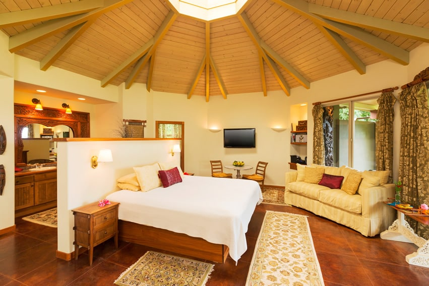 Bedroom suite at tropical resort with tall wood ceiling