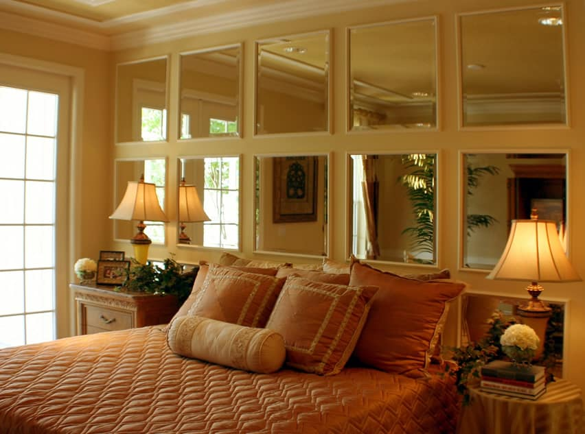 Bedroom with mirror paneled wall behind bed