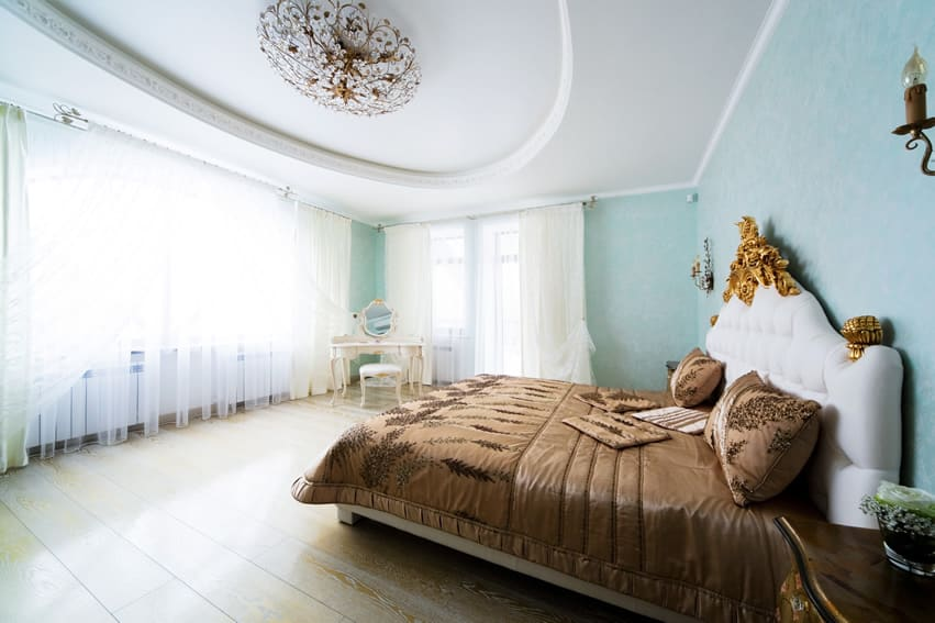 Designer bedroom with light blue walls sheer curtains