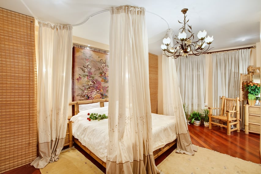 Four post bed with cream curtains bamboo furniture