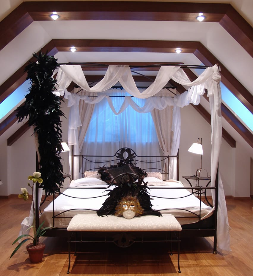 Impressive bedroom with four post bed exposed wood beam ceiling